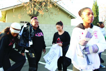 Brittney Smith, right, a CSUB alumna, joins her sorority sisters from Delta Sima Theta to pick up trash near Martin Luther King Jr. Park on Jan. 20, 2014