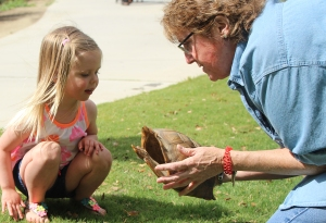 Terri Hayes, a CALM employee, teaches a little girl about the life cycle of a tortoise during the park's spring fling event on Apr. 18, 2014.