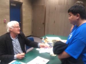 Christopher Enriquez, Nursing Major, talks to Charles Martinet after the Gamer Education Day after Martinet autographed his program.