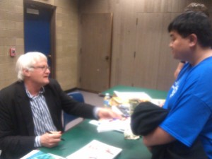 Christopher Enriquez, Nursing Major, talks to Charles Martinet after the Gamer Education Day after Martinet autographed his program.