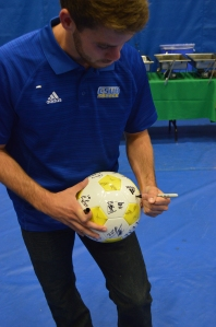 Eric Garza/The Runner Former soccer player and current grad assistant Scott Luedtke signing a soccer ball as a prize giveaway.
