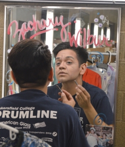 Eric Garza/The Runner Zachary Gonzalez, a junior communications major, applies make-up for his character Wilbur.
