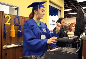 Adriana Vega/The Runner Julia Hughes, a CSUB Bookstore employee, shows off the blue undergraduate cap and gown while working at the register during the CSUB Grad Fair.